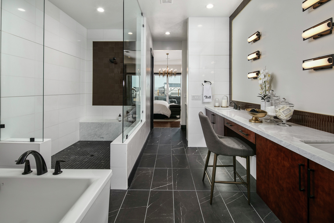 A modern bathroom with a long walk-in shower with a black tile floor.