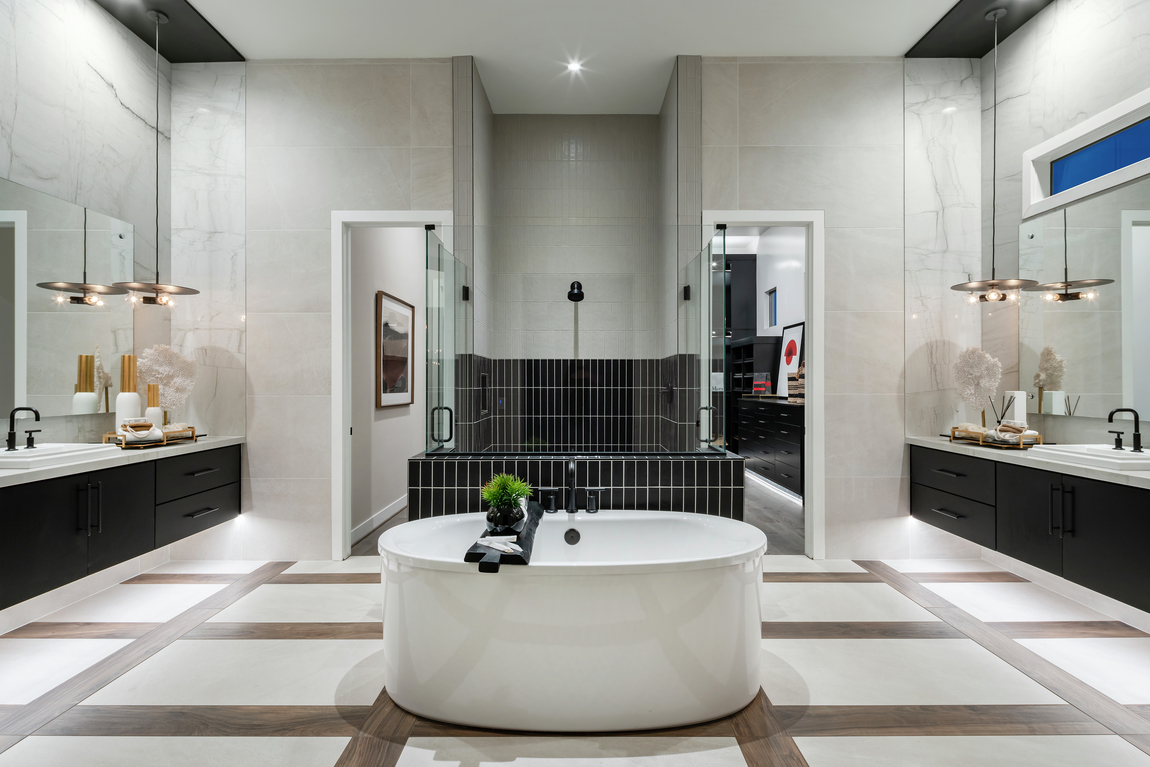 Large luxury primary bathroom with dual sinks, a freestanding bathtub and black accent tiles.