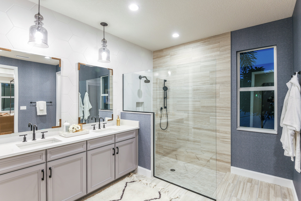 Primary bathroom with blue walls and a large and open walk-in shower.