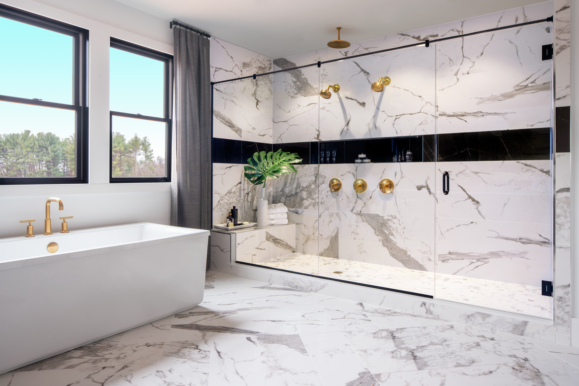 Primary bathroom with a freestanding bathtub and a large shower with gold faucets.