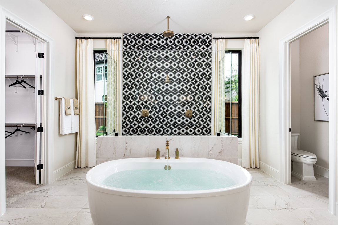 Luxury bathroom with gold hardware and an accent wall.