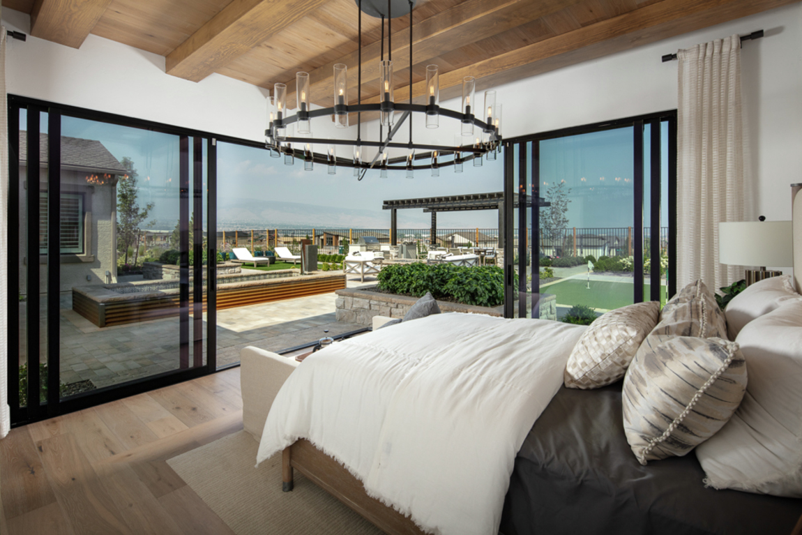 bedroom with outdoor transition and wood beam ceilings